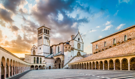 Famous Basilica of St. Francis of Assisi (Basilica Papale di San Francesco) with Lower Plaza at sunset in Assisi, Umbria, Italy.